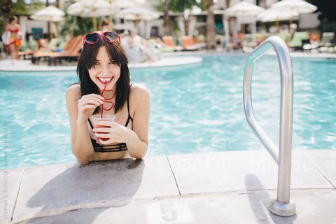 A portrait of a beautiful woman smiling drinking a smoothie in the pool